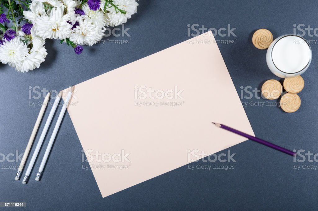 Light still life - sheet of beige paper, white and purple chrysanthemums, pencils, glass of milk and cookies on gray background. Concept of creativity and lightness. Top view mock up. stock photo