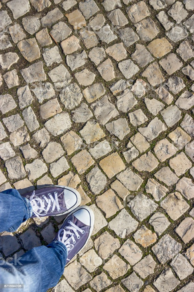 Light stone pavement and violet sneakers. Top view, free space stock photo
