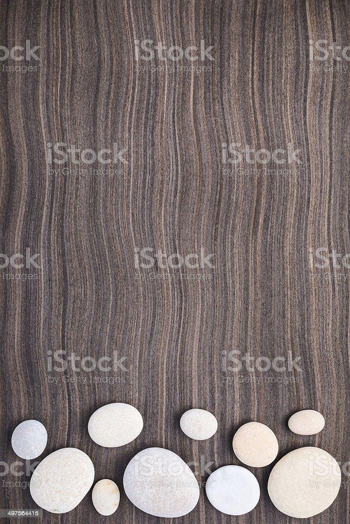 light stones on wooden ebony tree background stock photo