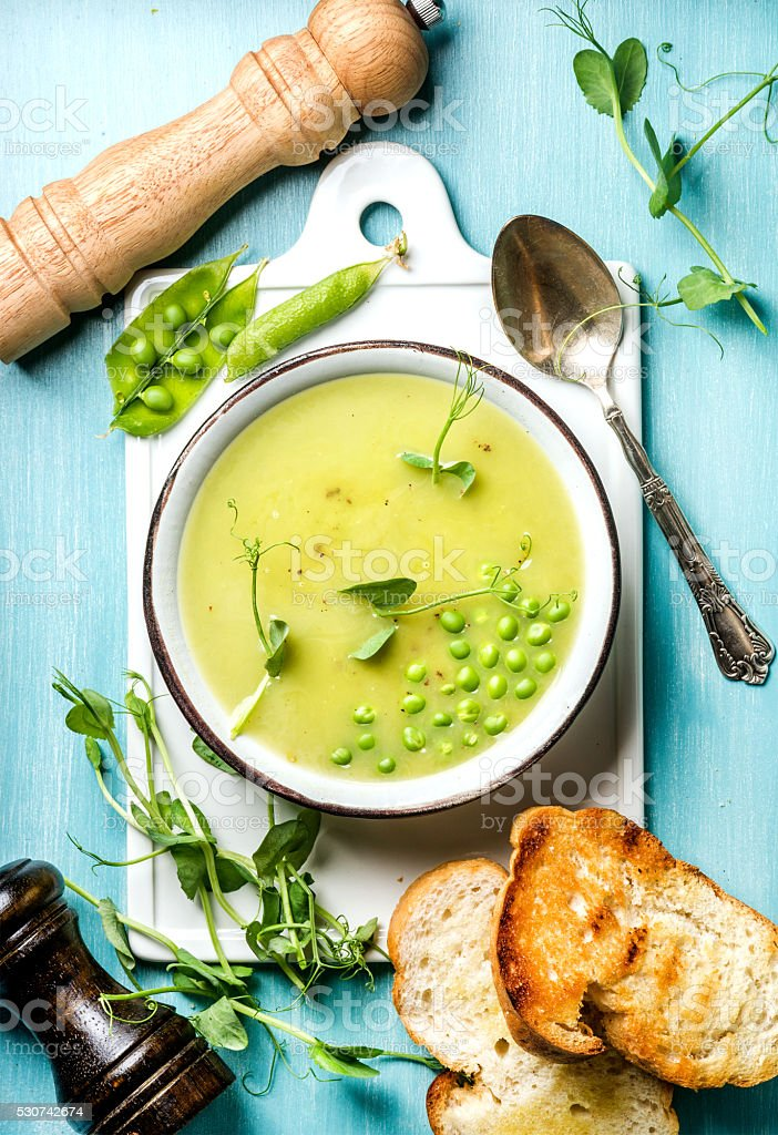 Light summer green pea cream soup in bowl with sprouts stock photo