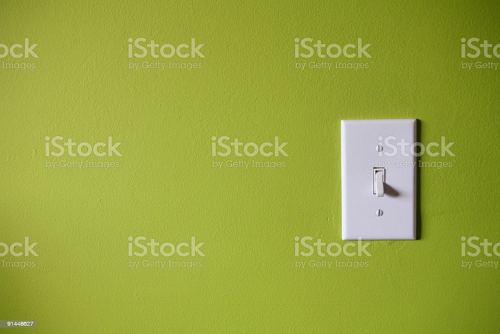Light switch in front of green background stock photo