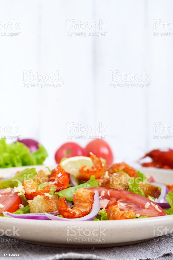 Light tasty salad with meat of a cancer, shrimps, lettuce, garlic croutons, tomatoes, red onions on a white background. Free space for an inscription. stock photo
