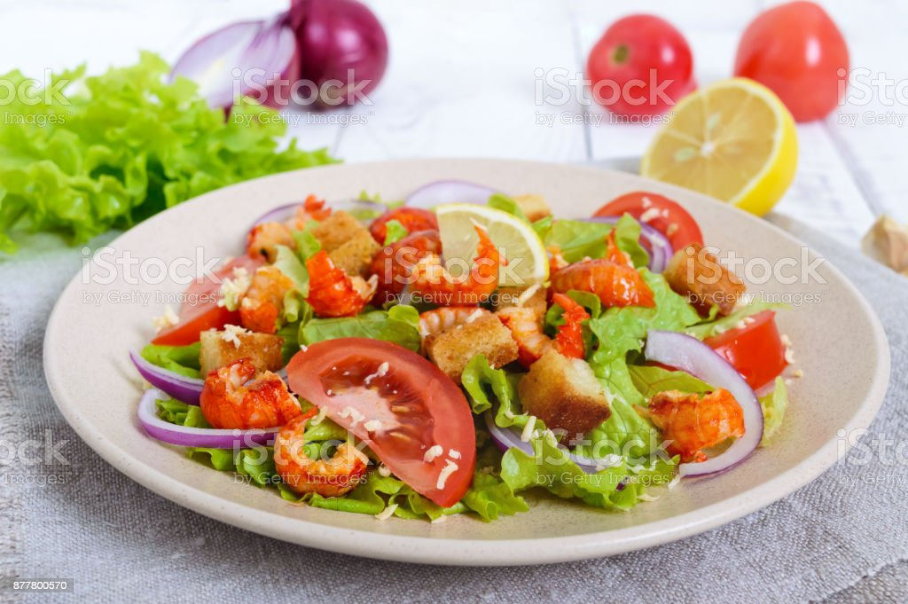 Light tasty salad with meat of a cancer, shrimps, lettuce, garlic croutons, tomatoes, red onions on a white background. stock photo