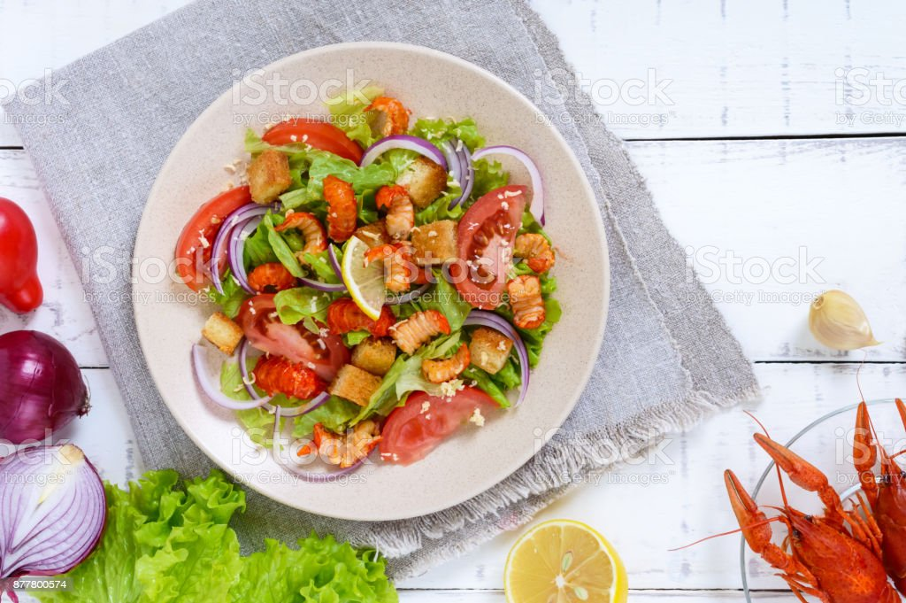 Light tasty salad with meat of a cancer, shrimps, lettuce, garlic croutons, tomatoes, red onions on a white background. The top view stock photo