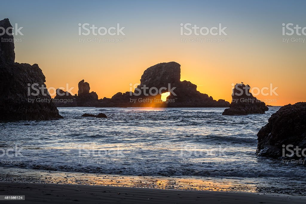 Light Through a Rock With Wave in Oregon stock photo