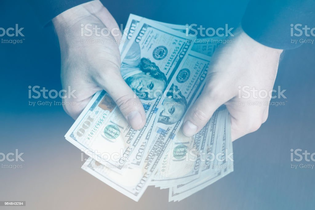 Light toning The white young man counts the money, one hundred new dollar bil royalty-free stock photo
