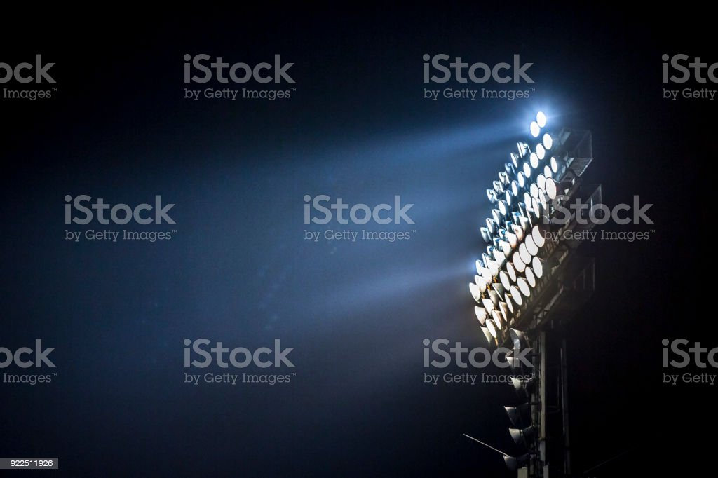 Light tower lit at a stadium during nightime. stock photo