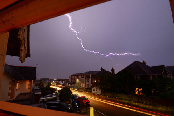 Light Trails and Lightning Over Rooftops stock photo