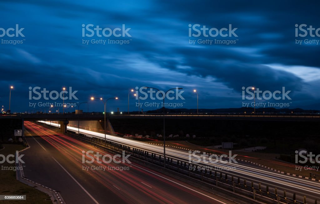 Light trails from fast moving cars on a highway stock photo