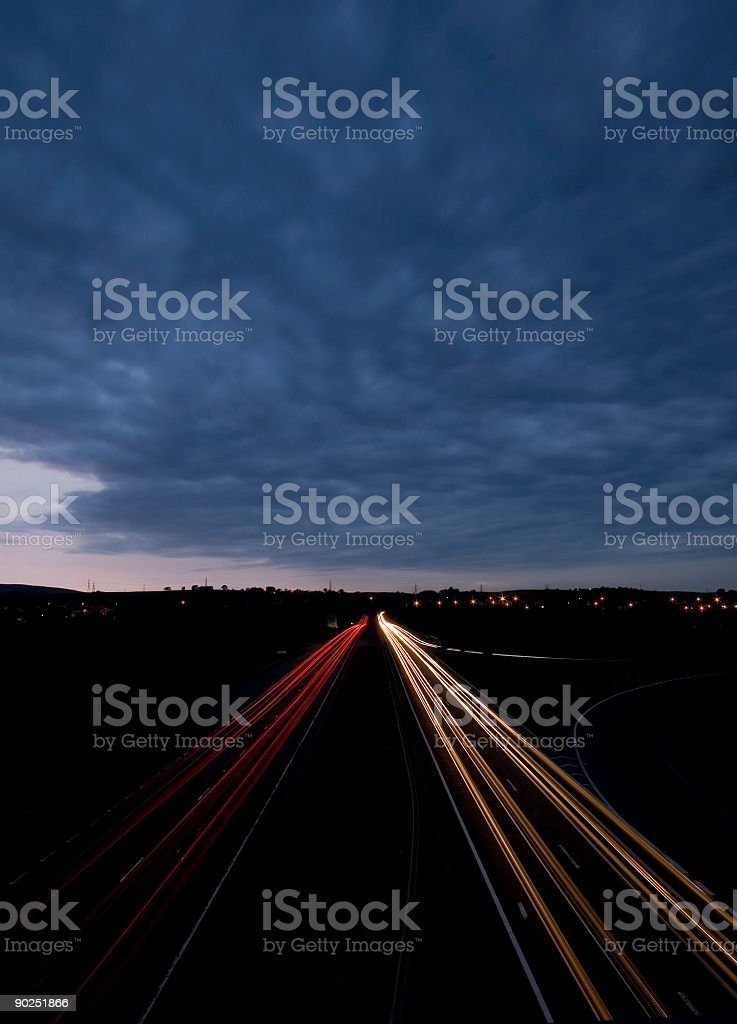 Light Trails from traffic at night beneath dramatic sky. stock photo