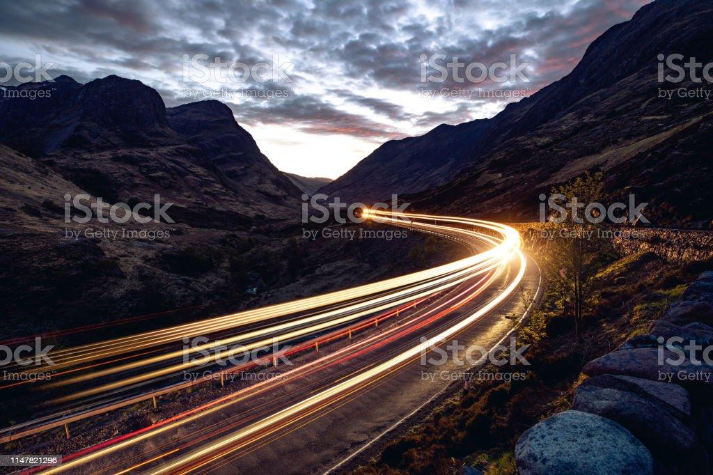 Leichte Wege in der Nacht auf einer abgelegenen Straße in Bergen - Lizenzfrei Abenddämmerung Stock-Foto