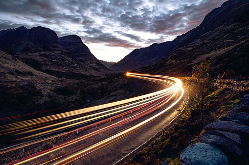 Light trails in the night on a remote road in mountains, Highlands, Scotland, UK.