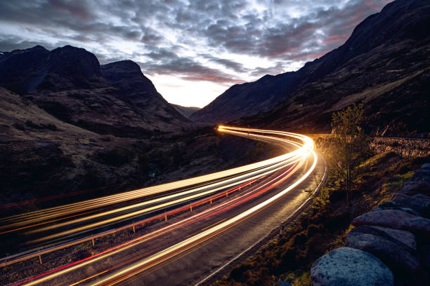 Light trails in the night on a remote road in mountains Light trails in the night on a remote road in mountains, Highlands, Scotland, UK. long exposure stock pictures, royalty-free photos & images