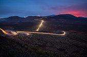 Light trails of cars during The Piton de la Fournaise volcano eruption at La Plaine des Sables in Reunion Island