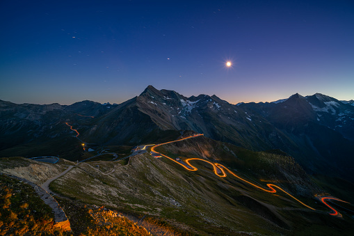 light trails on curvy high alpine road through european mountains at night with star shapped moon