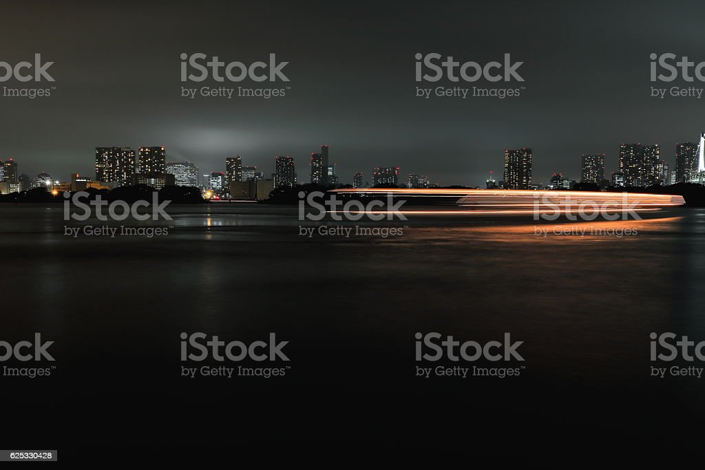 Light trails-ship under Rainbow Bridge crossing northern bay. Tokyo-Japan. 8020 stock photo