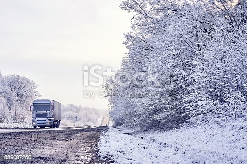 1127834626 istock photo light truck carries the load on a winter road along the forest 889087250