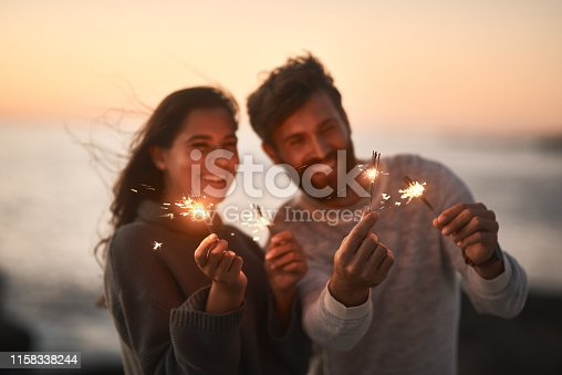Shot of a happy young couple having fun with sparklers on the beach at sunset