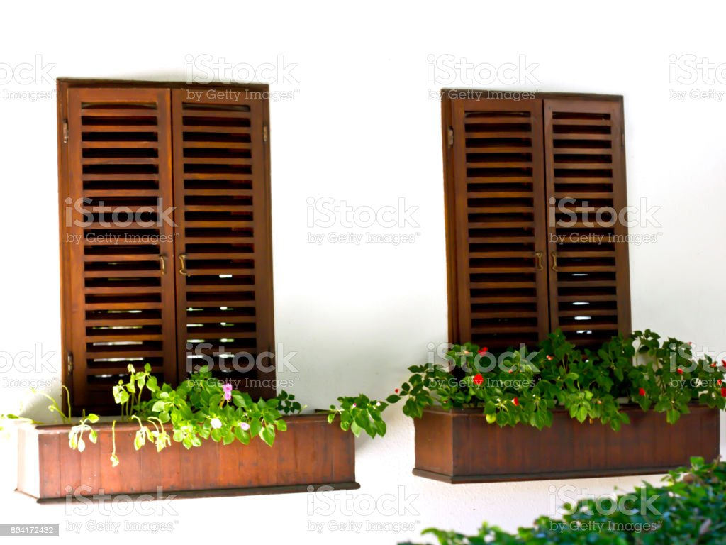 Light wall with the dark brown wooden shutters and wooden boxes with flowers royalty-free stock photo