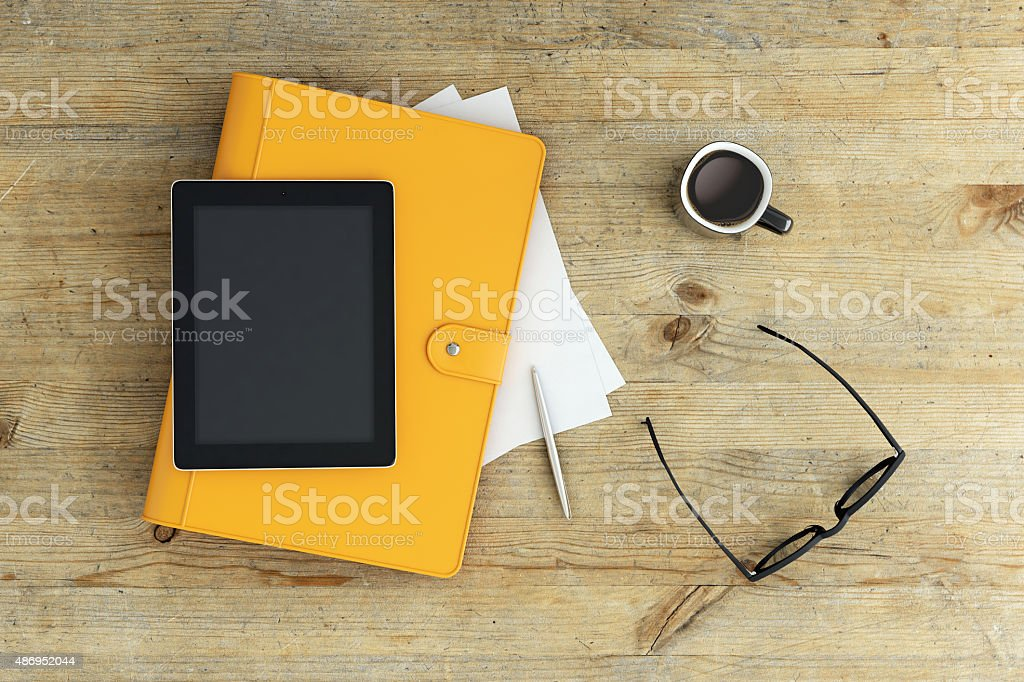 Light wood desk with a notebook and working setup stock photo