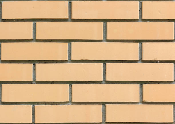 Light yellow brick wall of building close-up view stock photo