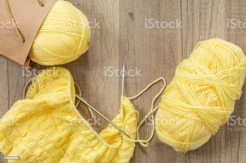 Light yellow knitting wool and knitting needles on wooden background royalty-free stock photo