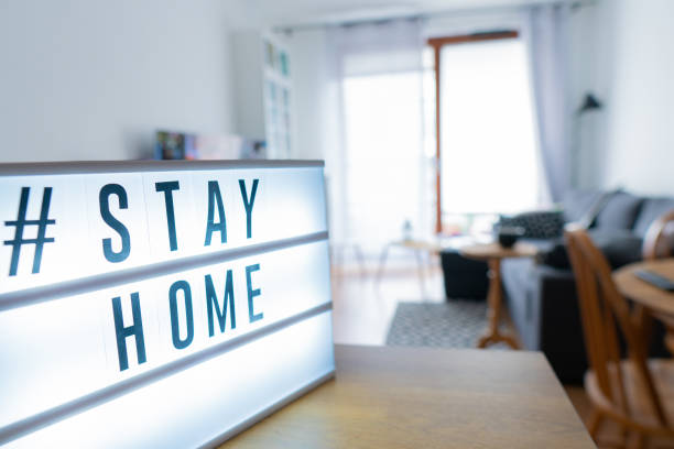 Lightbox sign with hashtag; Stay Home against the background of the interior of the apartment. Lightbox sign with hashtag; Stay Home against the background of the interior of the apartment. flatten the curve stock pictures, royalty-free photos & images