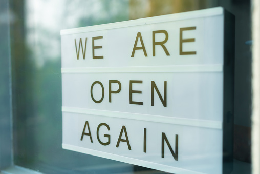 istock Lightbox with as sign we are open again behind a glass door of the cafe. We're open again after quarantine, video of small business owner. Please wear a face mask and keep your distance to protect 1222648152