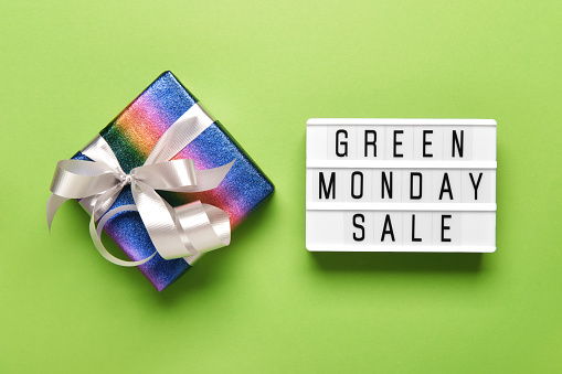 Lightbox with GREEN MONDAY SALE text on green paper background and LGBTQ community rainbow flag colors gift box