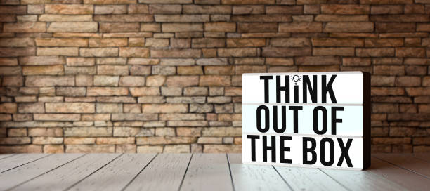 lightbox with message THINK OUTSIDE THE BOX in front of brick wall - 3D rendered illustration stock photo