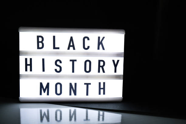 Lightbox with text BLACK HISTORY MONTH on dark black background with mirror reflection. Message historical event stock photo