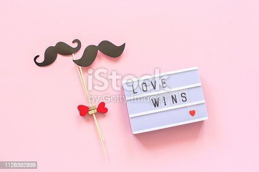 Lightbox with text Love wins and couple paper mustache props on pink background. Concept Homosexuality gay love National Day Against Homophobia or International Gay Day Top view Greeting card
