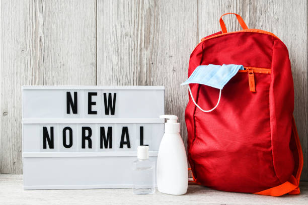Lightbox with text NEW NORMAL protective face mask and sanitizer. Back to school. Books falling from backpack. Social distancing stock photo