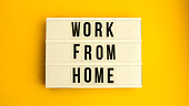 istock lightbox with text WORK FROM HOME in front yellow background, copy space, banner for freelance coronavirus quarantine isolation 1213483772