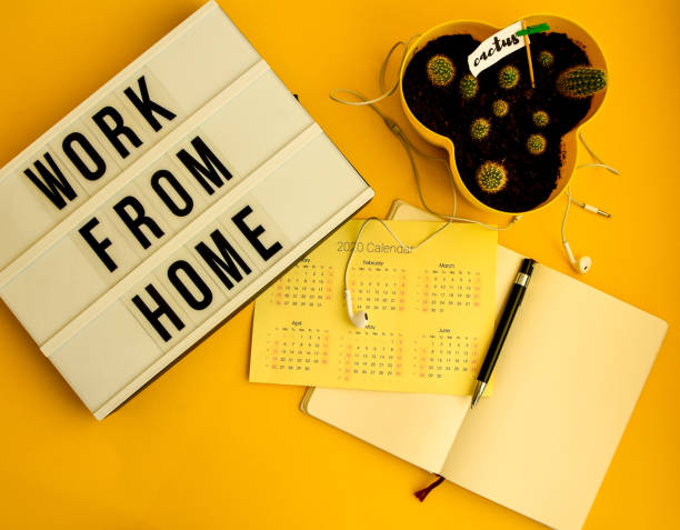 lightbox with text WORK FROM HOME with notebook pen and calendar 2020 TO DO list, copy space on yellow background, quarantine and isolation HOME OFFICE stock photo