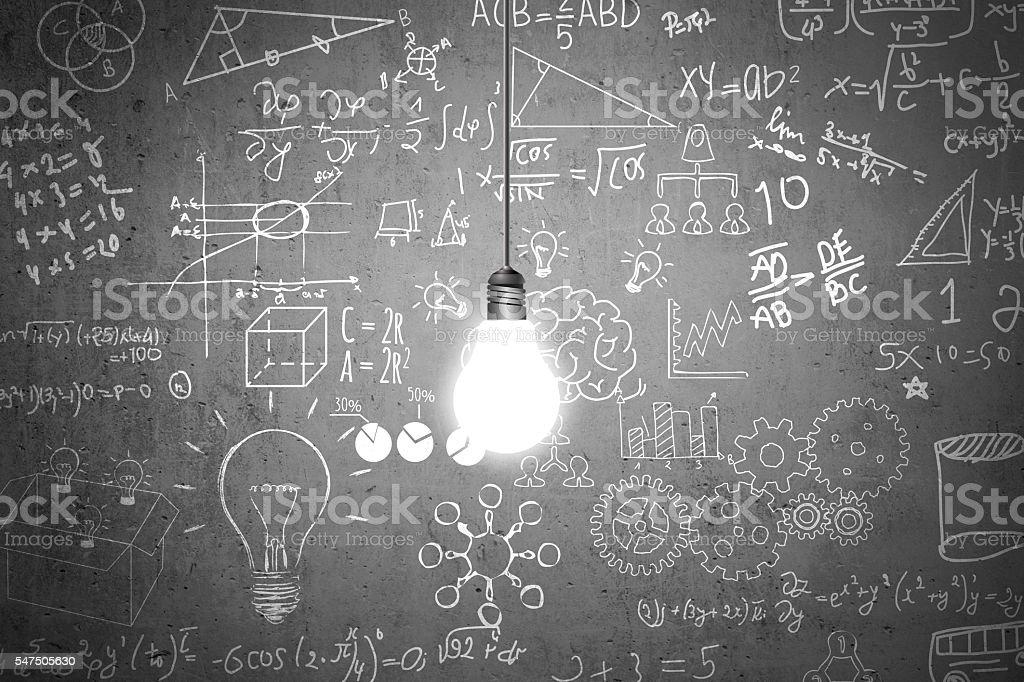 Lightbulb and mathematical symbols on dirty wall stock photo