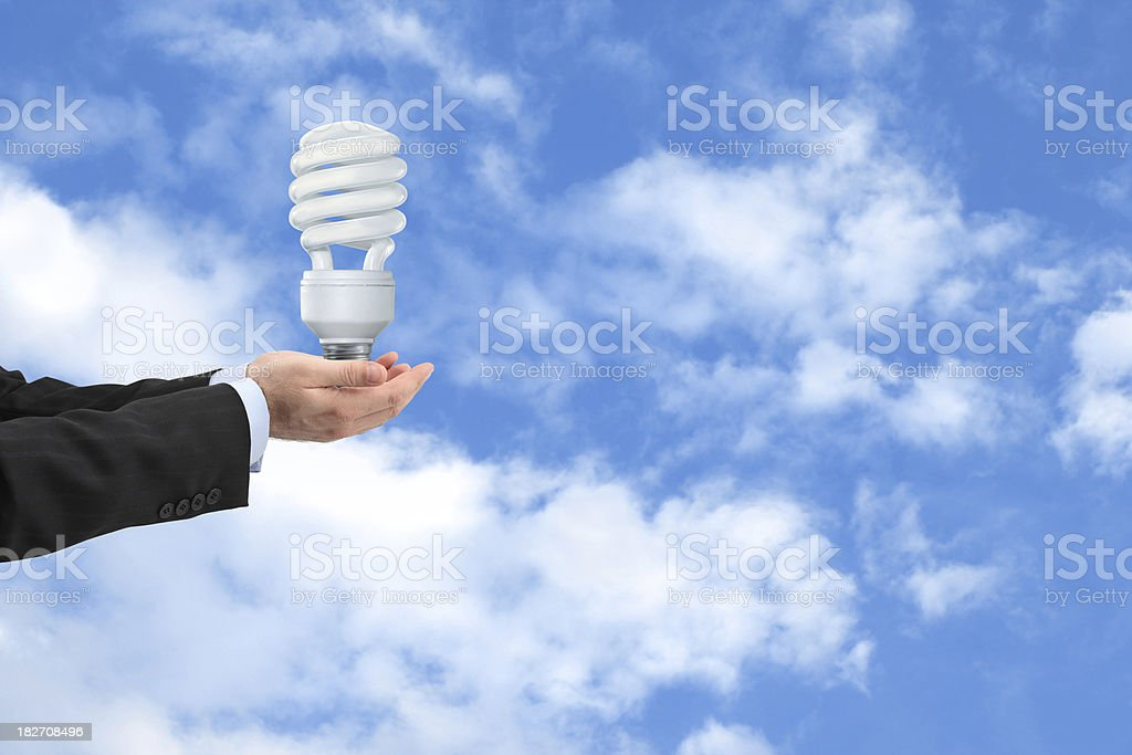 Lightbulb in Hands Compact fluorescent lightbulb in the businessman hands. Adult Stock Photo