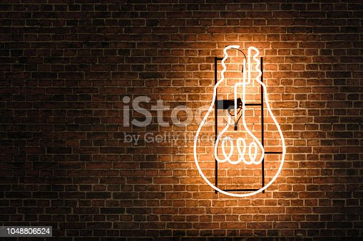 Lightbulb neon on the empty brick wall with copy space