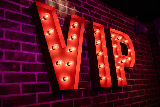 VIP Lightbulb Sign VIP red lightbulb sign on a brick wall in an indoor establishment. first class stock pictures, royalty-free photos & images