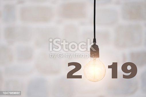 Lightbulbs on wall background writing 2019, idea concept