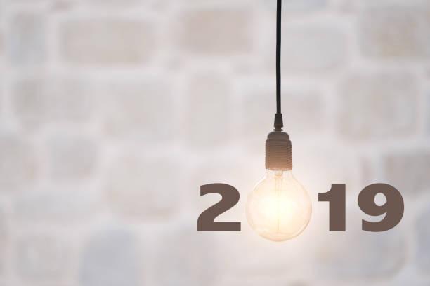 glühbirnen auf wand hintergrund schreiben 2019, idee konzept - ideen für silvester stock-fotos und bilder