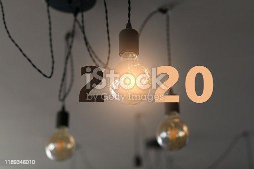 Lightbulbs on wall background writing 2020, idea concept