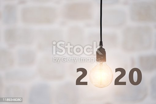 Lightbulbs on wall background writing 2020, idea concept