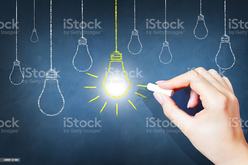 Lightbulbs suspended from wires drawn on blackboard stock photo