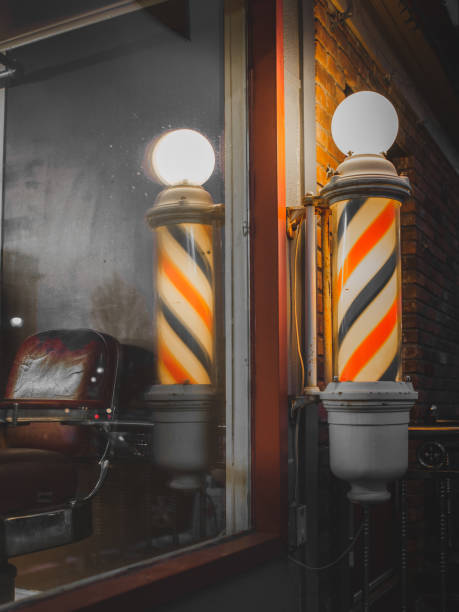 Lighted Barber Shop Pole and Antique Barber Chair in Window stock photo