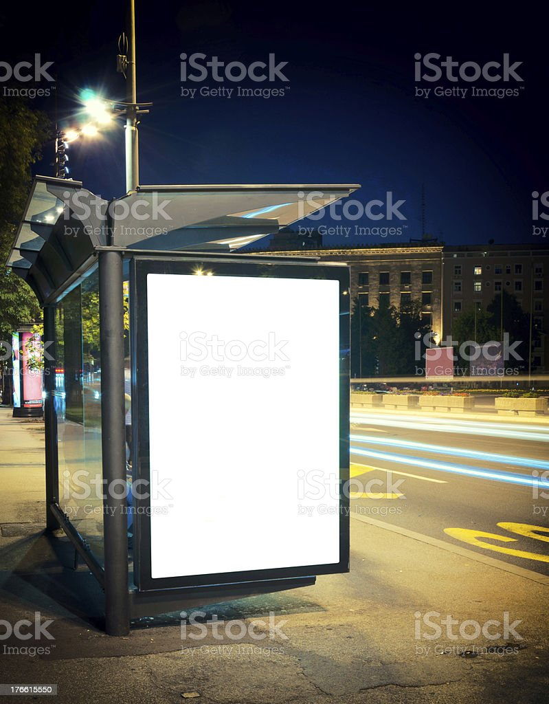 Lighted bus station on an empty city street at night stock photo