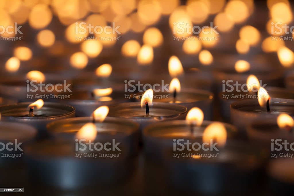 Lighted candle amongst many flaming tea light candles. Beautiful romantic candlelight. stock photo