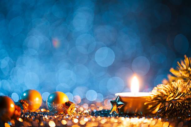 lighted candle and christmas decorations on defocused blue background - luz da vela - fotografias e filmes do acervo