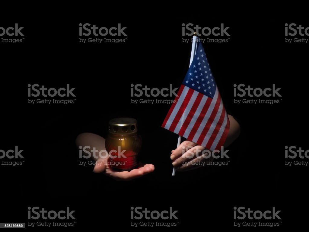 Lighted candle and female hands with USA flag stock photo