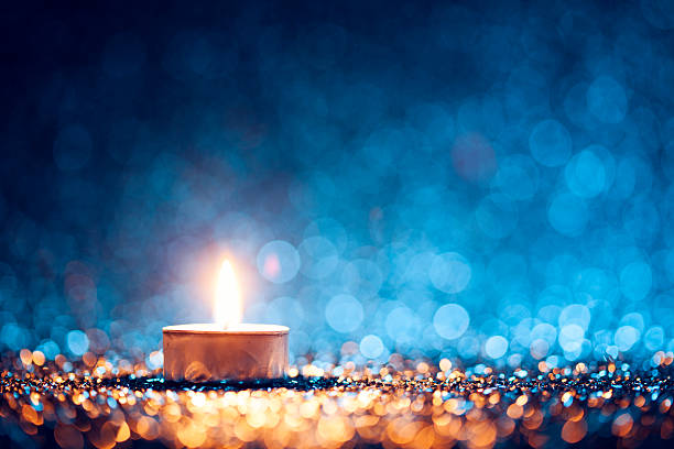 Lighted candle on defocused blue background - Christmas Tea Light - Photo